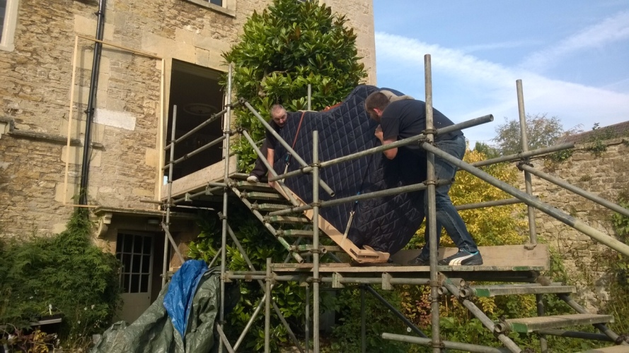 A Grand Piano Removal in action going up scaffolding into a house